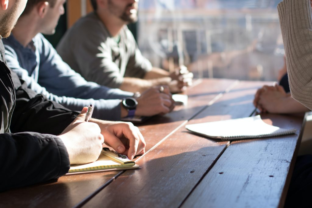 people sitting on chair in front of table writing a brand manifesto